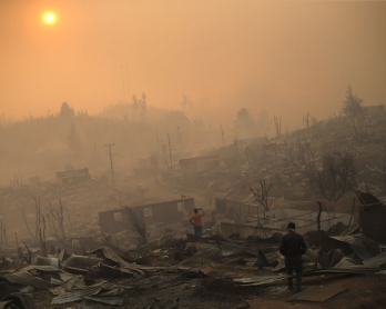 People walk amid the remains of burnt down buildings after a forest fire in Santa Olga, 240 kilometres south of Santiago, on January 26, 2017.
