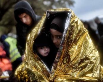 Niños cubiertos con una manta de emergencia tras llegar a la costa de Lesbos en octubre