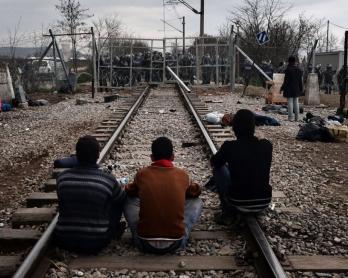 Los refugiados esperan sobre la vía del tren que conecta Grecia con Macedonia, delante de la frontera bloqueada por la policía macedonia el 29 de febrero de 2016